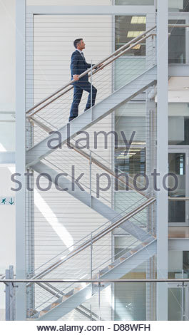 Businessman ascending stairs in office - Stock Photo