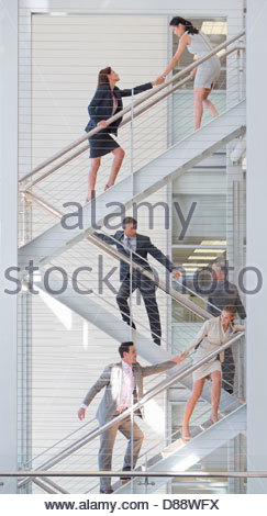 Business people holding hands on stairs in office - Stock Photo