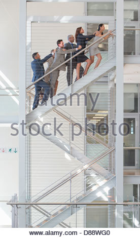 Connected business people ascending stairs in office - Stock Photo
