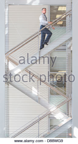Portrait of confident businessman ascending stairs in office - Stock Photo