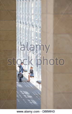 Businessman and businesswoman talking in lobby of modern office - Stock Photo
