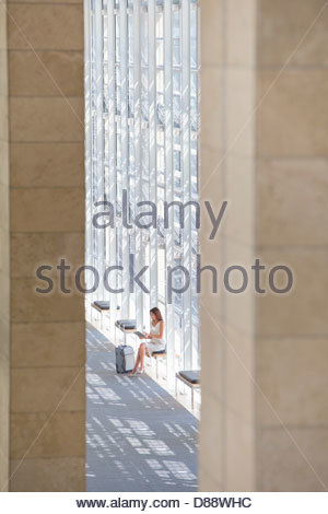 Businesswoman with suitcase using digital tablet in lobby of modern office - Stock Photo