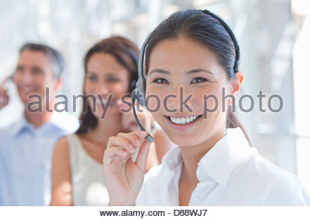Close up portrait of smiling businesswoman wearing headset - Stock Photo
