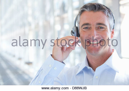 Close up portrait of smiling businessman wearing headset - Stock Photo