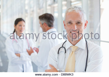 Close up portrait of smiling doctor in hospital corridor - Stock Photo