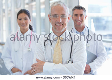 Close up portrait of smiling doctors in hospital corridor - Stock Photo