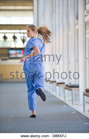 Nurse running down hospital corridor - Stock Photo