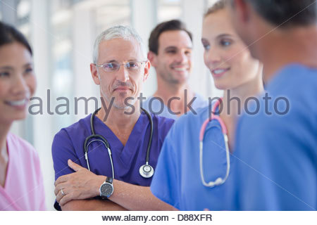 Portrait of confident doctor among co-workers - Stock Photo