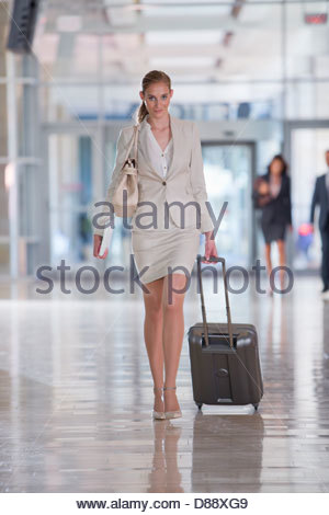 Portrait of confident businesswoman pulling suitcase in airport - Stock Photo