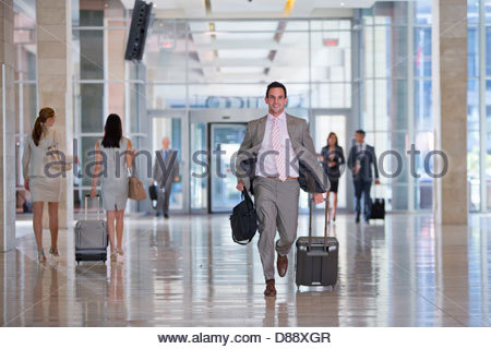 Smiling businessman carrying briefcase and pulling suitcase in airport - Stock Photo