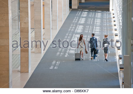 Business people walking in lobby of modern office - Stock Photo