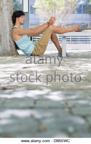 Young man with digital tablet sitting on sidewalk with foot on bench - Stock Photo