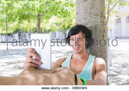 Smiling young man using digital tablet against tree in park - Stock Photo