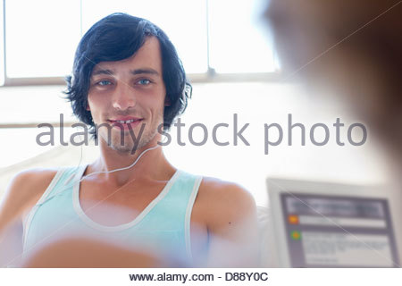 Portrait of smiling young man wearing headphones - Stock Photo