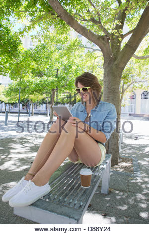 Smiling young woman drinking coffee and using digital tablet on park bench - Stock Photo