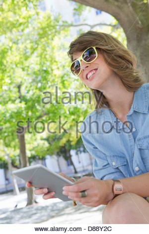 Smiling young woman wearing sunglasses and using digital tablet in park - Stock Photo
