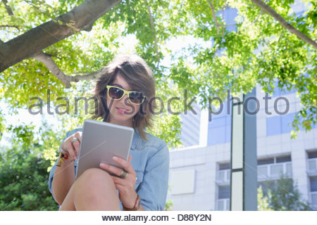 Young woman wearing sunglasses and using digital tablet below tree in park - Stock Photo