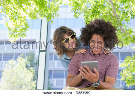 Smiling young couple using digital tablet in urban park - Stock Photo