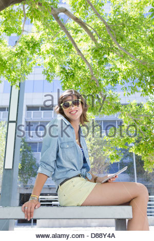 Portrait of smiling young woman wearing sunglasses and using digital tablet on urban park bench - Stock Photo