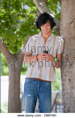 Smiling young man text messaging with cell phone in park - Stock Photo