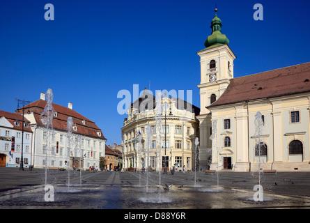 Brukenthal Palace, left. City Hall, Catholic garrison church, on the Grand Boulevard, Piata Mare, Sibiu, Romania - Stock Photo
