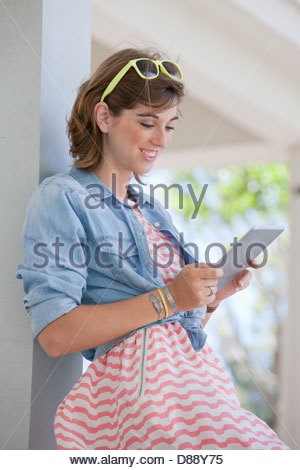 Smiling young woman using digital tablet - Stock Photo