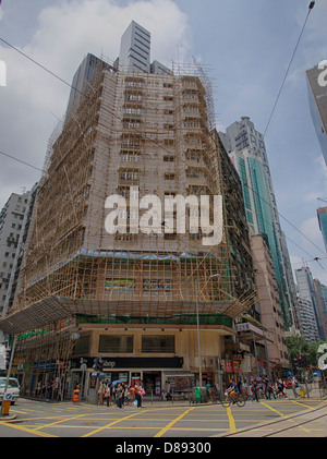A building in Wan Chai currently going under renovation.  It is covered in bamboo scaffolding traditionally used - Stock Photo