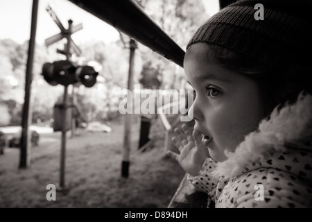A young girl looks out of a window on the Puffing Billy steam train in Melbourne, Victoria, Australia - Stock Photo