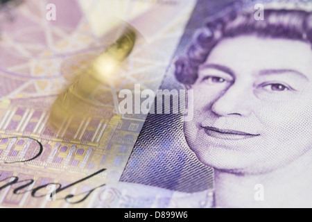 A pound coin spinning on a twenty pound note. - Stock Photo