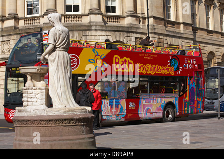 Bath city sightseeing bus tour going past the Water Goddess Rebecca water fountain at Bath, Somerset UK in April - Stock Photo