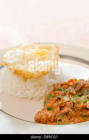 pork fried with chili pepper and curry sauce and fried egg over rice on dish - Stock Photo