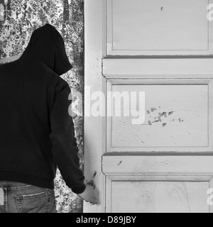 Hooded figure exiting through the door of an abandoned house. - Stock Photo