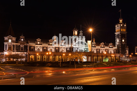 Dunedin Railway Station during RWC2011, including topiary rugby ball in front of station and motion blur of passing - Stock Photo