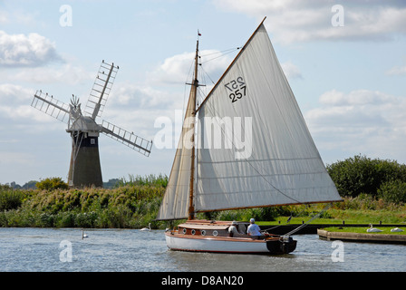 Sailing yacht passing windmill on river Thurne, Norfolk Broads, England - Stock Photo