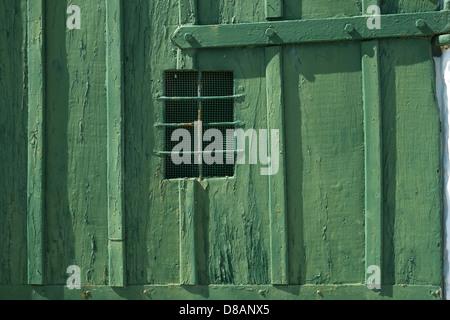 Barred window in green boathouse door Menorca, Spain - Stock Photo