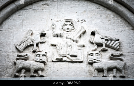 Big wall in church showing five fictional characters. Two birds on top of two lions, sitting man in middle. Primitive - Stock Photo
