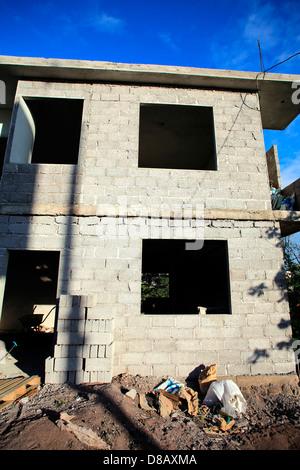 Basic concrete block building under construction on San Cristobal Island,  Galapagos Islands - Stock Photo