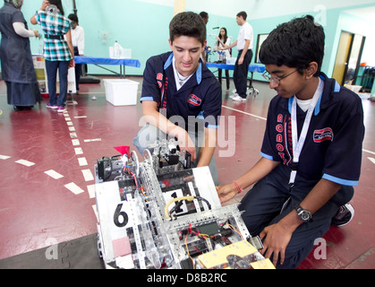 Multi-ethnic group of high school robotics club students give a demonstration during a science fair at school in - Stock Photo