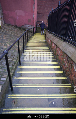 An old man walks down wet steps in Stockport, England - Stock Photo