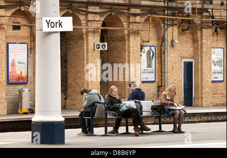 Passengers people waiting for a train on the platform, York railway station, Yorkshire UK - Stock Photo