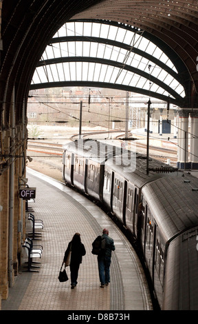 A couple of people catching a train on the platform, York railway station, Yorkshire UK - Stock Photo