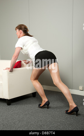 woman moving office furniture pushing a settee into place stock photo - Office Chair For Short Person