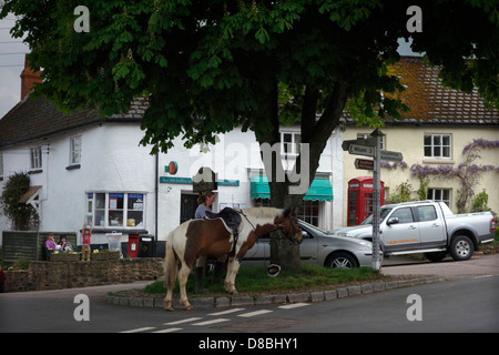 Kentisbeare village centre, Devon with ponies, village stores and post office and red telephone kiosk - Stock Photo