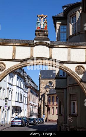 Archway with a crucifixion group near Liebfrauenbasilika church, Trier, Rhineland-Palatinate, Germany, Europe - Stock Photo