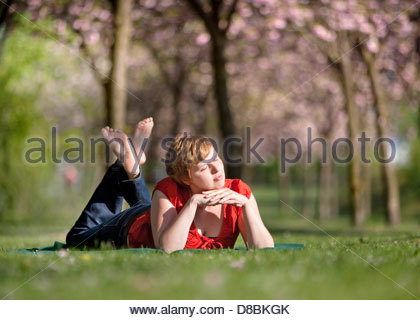 Young woman taking sun bath in a garden and day dreaming, Berlin, Germany - Stock Photo