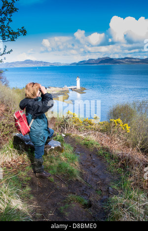 Lady walker enjoying the view to Rubha Nan Gall Lighthouse, North of Tobermory on the isle of Mull - Stock Photo