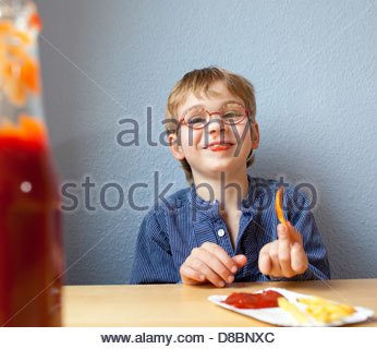 Portrait of a boy having French fries and smiling - Stock Photo