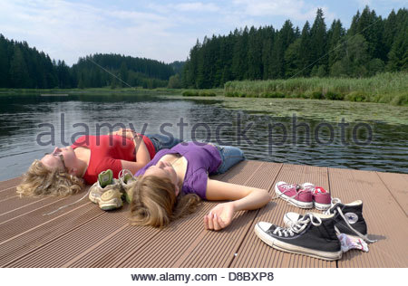Two young lying on a pier and taking sun bath - Stock Photo