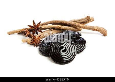 Liquorice roots, star anise and liquorice wheels on white background - Stock Photo