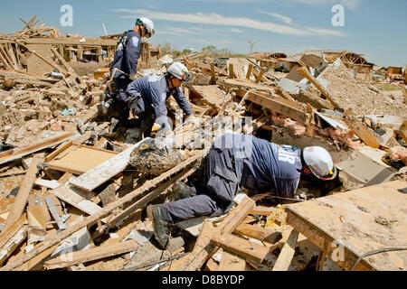 FEMA Urban Search and Rescue teams search house to house for survivors in a destroyed neighborhood in the aftermath - Stock Photo